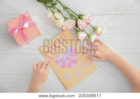 Little girl preparing greeting card for her mommy on Mother's Day at table poster
