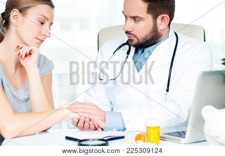 Doctor and patient. Hand of doctor reassuring her woman patient