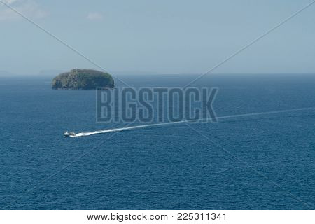 Aerial view of speedboat in sea, tropical island. Motorboat floating in a turquoise blue sea water, Bali, Indonesia. Travel concept.