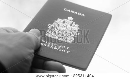 Persons hand holding and giving passport of Canada