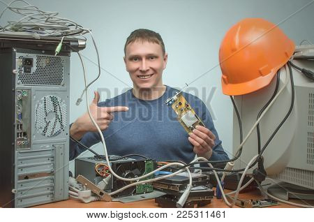 Happy Computer technician engineer holding in hands a video card and is installing it to a computer or showing broken PC part.