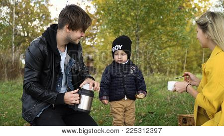 Young family with son at a picnic in the park on a sunny day. Family having picnic outdoors. Young smiling family doing a picnic on an autumns day. Family picnicking together.