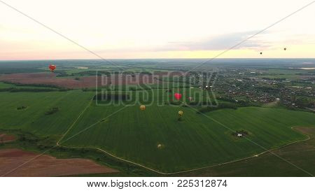 Aerial view Hot air balloons in the sky over a field in the countryside in the beautiful sky and sunset. Balloon silhouette with sunrise, Aerostat fly in the countryside.