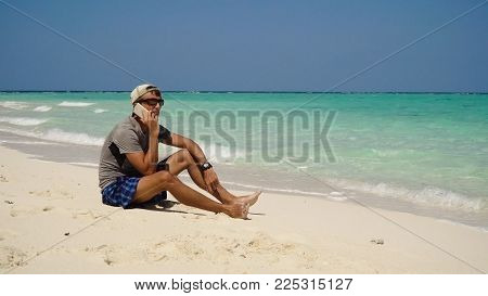 Man talking on the mobile phone at the beach. Man talking on cell phone and sitting along beach. Beach, sea, sand, wave. Philippines, Travel concept.