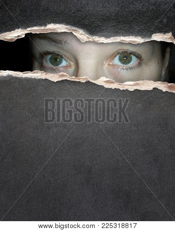 A look from darkness. Eyes of an old woman looking into a hole in a paper