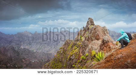 Man hiker with backpack sitting on the mountain top and looking down to the valley. Stunning arid landscape on Santo Antao island, Cabo Verde.