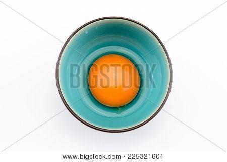 Egg yolk in bowl on white background