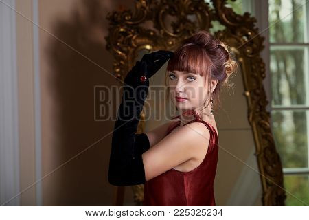 Elegant retro woman in red dress with long gloves and a precious ring. Lovely woman retro portrait. Beautiful young women in vintage interior.
