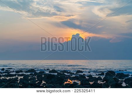 Bright glow of sun behind cloads on a hazy morning ovelooing rocky coastal landscape.Sunrise at Koh Samui along coral coastline.