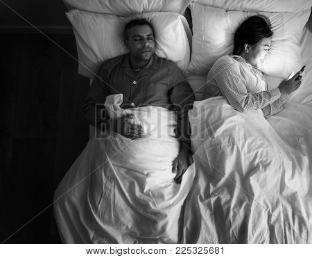 Interracial couple on the bed woman using her phone
