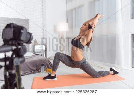 Feeling vigorous. Nice cheerful muscular dark-haired young blogger smiling and doing sport while sitting on the carpet and making a video for her blog