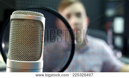 man creative musician at studio works by playing, singing and recording guitar with notebook and microphone indoor in modern 4k