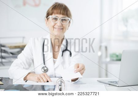 Elder Oculist With Glasses Holding A Prescription For Glaucoma Medicine