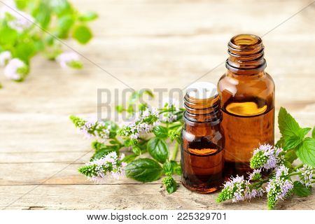 Peppermint essential oil and peppermint flowers on the wooden table