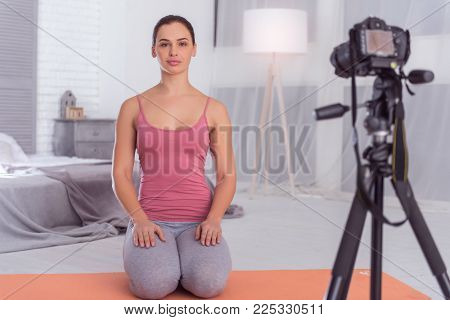 In high spirits. Good-looking cheerful slim muscular young blogger smiling and sitting on the carpet while making a video for her blog