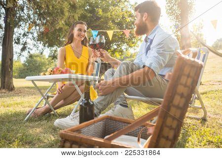 Young and beautiful couple in love toasting with red wine while sitting down on folding chairs during romantic picnic in the countryside