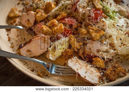 Caesar salad closeup on a wooden platter