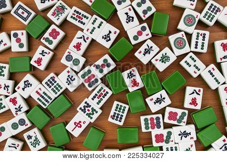 White-green tiles for mahjong on a brown wooden background. No empty place.