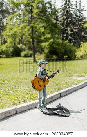 KYIV, UKRAINE May 01, 2016: Boy playing on acoustic guitar outdoors. Little street musician. Toned photo