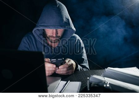 a male hacker is sitting in a dark room at the table and something is typing in the phone