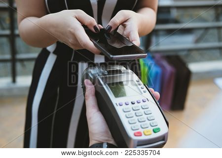 Woman Use Smartphone To Make Mobile Payment With Electronic Reader. Customer Paying With Near Field
