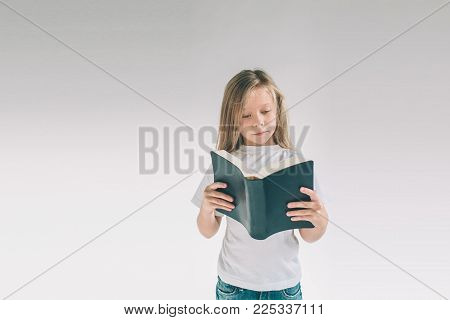 girl in white t-shirt is reading a book on a white background. Child likes to read books.