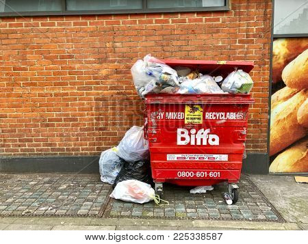 LONDON - FEBRUARY 5, 2018: Overflowing mixed recyclable waste disposal bin outside a supermarket in West Hampstead, London, UK.