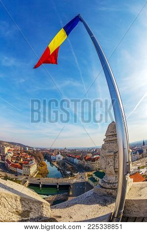 ORADEA, ROMANIA - JANUARY 27, 2018: Aerial view from the city hall tower over Oradea town center with historic buildings, Crisul Repede and churches. Romanian national flag in front.