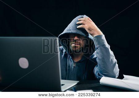 An experienced hacker works in a dark room