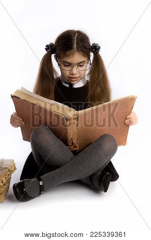 A little schoolgirl in glasses holds an enormous old book in her hands and reads it sitting on the floor