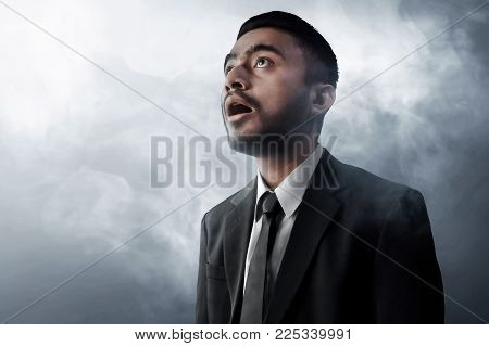 Business man amazed expression on smoke background