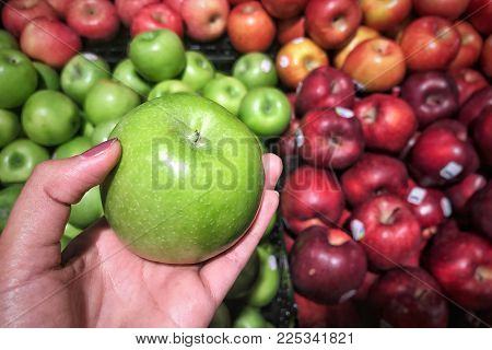 The girl picked the apple in the market. Woman's hand hold green apples