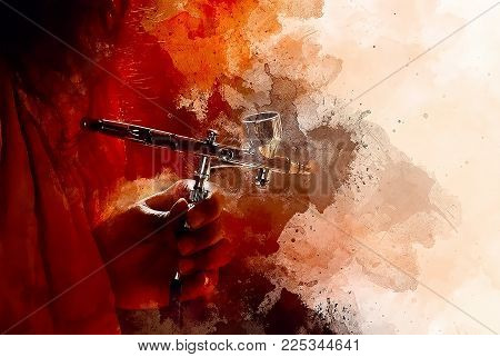 hand holding airbrush gun in painting process and softly blurred watercolor background