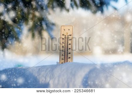 Thermometer in the snow. In the background, Spruce in the snow. Winter. Winter concept.