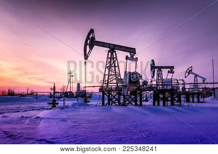 Pump jack, wellhead and pipeline during sunset in the oilfield. Winter period. Oil and gas concept. Toned.