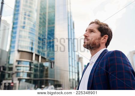 Ambitious and successful young businessman wearing a blazer deep in thought while standing alone in the city