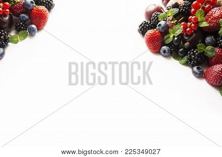 Mix berries on a white. Berries and fruits with copy space for text. Black-blue and red food. Ripe blackberries, blueberries, strawberries, red currants and plums on white background. Background berries. Various fresh summer berries. Top view.