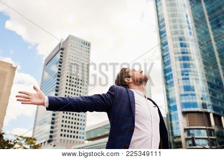 Ambitious young businessman standing in front of office buildings with his arms raised to the sky