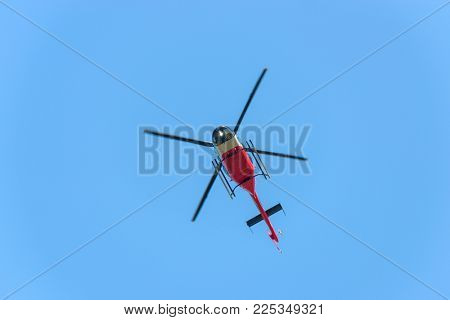 Red and white helicopter in flight against blue sky