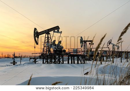 Pump jack, wellhead and pipeline during sunset in the oilfield. Winter period. Oil and gas concept. Blurred grass foreground.