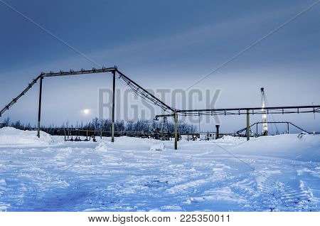 Pump jack, wellhead, pipeline and oil rig during moon eclipse in the oilfield. Winter period. Oil and gas concept. Toned.