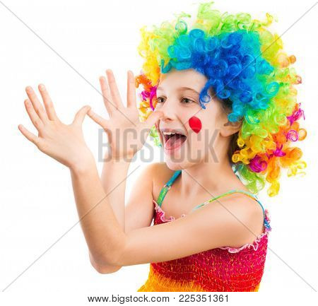 Little girl in rainbow clown wig fooling around isolated on white background
