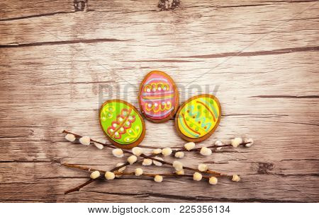 Easter composition with spring flowers and easter cookies on wooden background. Easter concept. Flat lay, top view.
