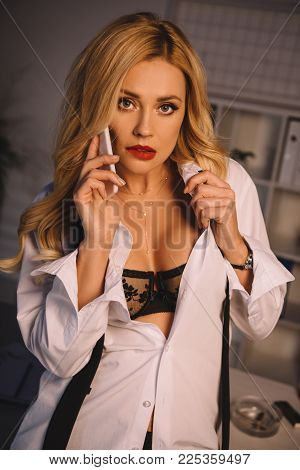 Sexy Woman In Unbuttoned Shirt And Black Bra Talking By Smartphone And Looking At Camera