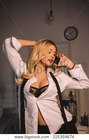 Sexy Woman Posing In Unbuttoned Shirt And Black Bra And Talking By Smartphone