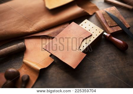 Leather craft or leather working. beautifully colored tanned leather on leather craftman's work desk with working tools.
