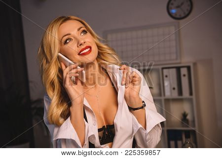 Smiling Sexy Woman In Unbuttoned Shirt And Black Bra Talking By Smartphone In Office