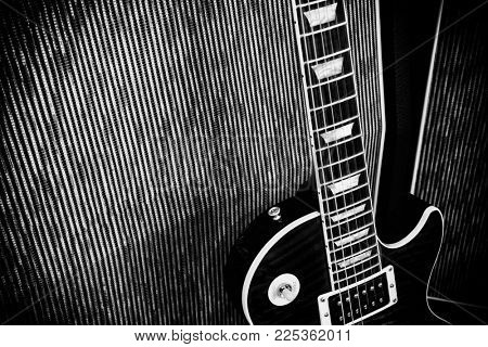 Electric guitar leaning against an amplifier - black and white