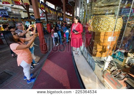 DUBAI, UNITED ARAB EMIRATES - JAN 02, 2018: Tourists making photo's of the largest golden ring in the world, it weighs almost 64 kilograms. The ring is in the guinness book of records. It is located in the City of gold in Dubai.