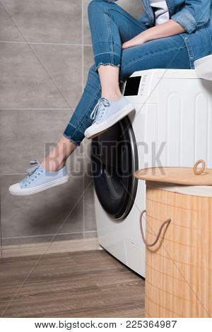 Partial View Of Housewife Sitting On Washing Machine At Home